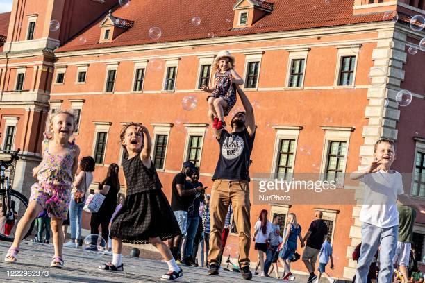 Families are seen playing with soap bubbles as Poles enjoy first hot day after particularly cold spring in Krakowskie Przedmiescie by the Royal...