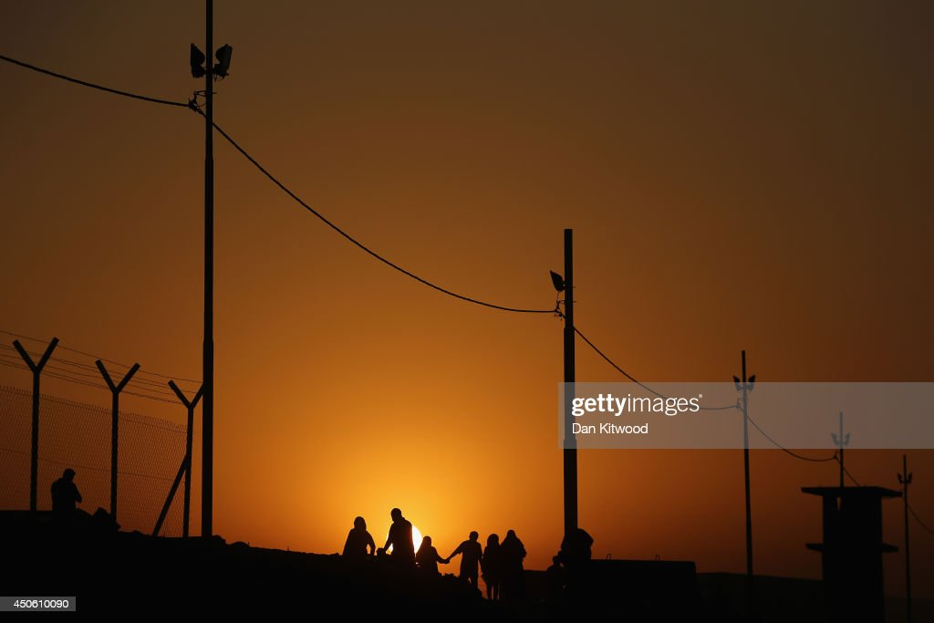 Families arrive at a Kurdish checkpoint at sunset next to a temporary displacement camp on June 14, 2014 in Kalak, Iraq. Thousands of people have fled Iraq's second city of Mosul after it was overrun by ISAS (Islamic State of Iraq and Syria) militants. Many have been temporarily housed at various IDP (internally displaced persons) camps around the region including the area close to Erbil, as they hope to enter the safety of the nearby Kurdish region.