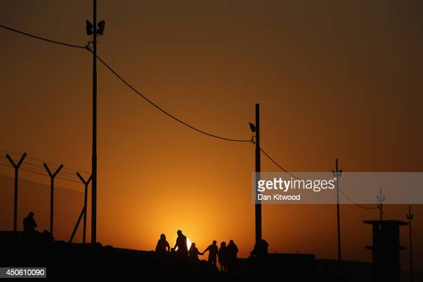 Families arrive at a Kurdish checkpoint at sunset next to a temporary displacement camp on June 14, 2014 in Kalak, Iraq. Thousands of people have...