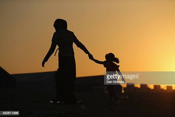 Families arrive at a Kurdish checkpoint at sunset next to a temporary displacement camp on June 14 2014 in Kalak Iraq Thousands of people have fled...