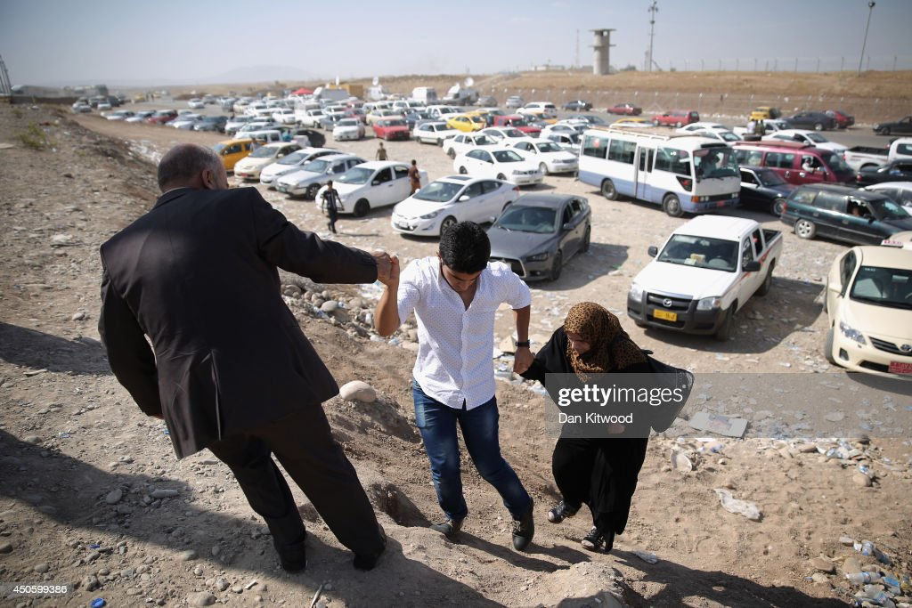 Families arrive at a Kurdish checkpoint next to a temporary displacement camp on June 14, 2014 in Kalak, Iraq. Thousands of people have fled Iraq's second city of Mosul after it was overrun by ISAS (Islamic State of Iraq and Syria) militants. Many have been temporarily housed at various IDP (internally displaced persons) camps around the region including the area close to Erbil, as they hope to enter the safety of the nearby Kurdish region.