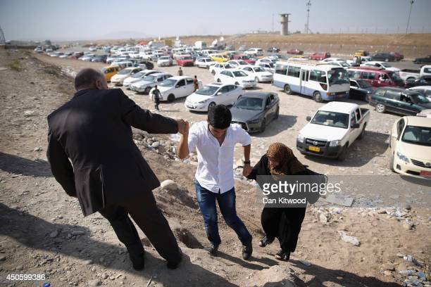 Families arrive at a Kurdish checkpoint next to a temporary displacement camp on June 14, 2014 in Kalak, Iraq. Thousands of people have fled Iraq's...
