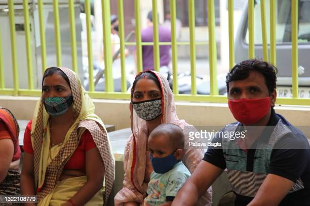 Families await their turn to get vaccinated at the Primary Health Center on June 1,2021 in Allika Village,India. As India battles a second wave of...