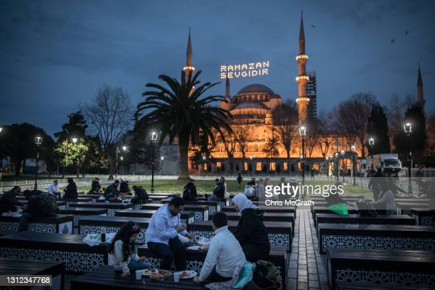 Families break their fast in front of the Blue Mosque on April 13, 2021 in Istanbul, Turkey. Millions of Muslims around the world began observing the...