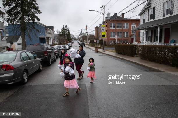 "Families carry home free bagged meals given out as part of Stamford Public Schools' ""Grab and Go Meals for Kids"" program, which is part of the city's..."