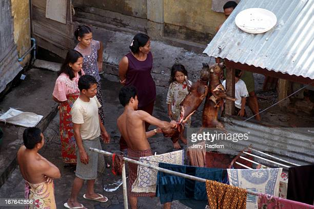 Families carve chunks from cooling dog carcasses at a communal home shared by the families of several policemen in Phnom Penh They cooked the dogs...