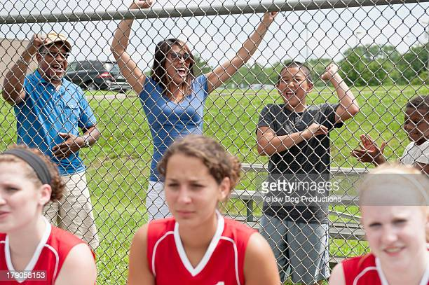 families cheering teen softball players - softball sport stock pictures, royalty-free photos & images
