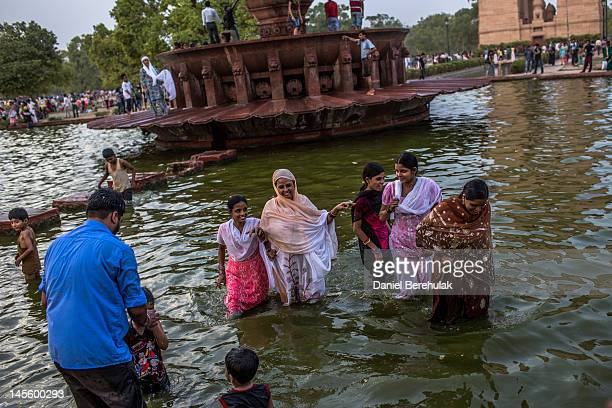 Families cool off in a pond as they and others gather at the India Gate monument on June 2 2012 in New Delhi India A Heat wave is continuing across...