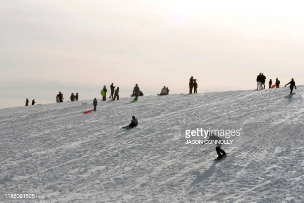 Families enjoy fresh new snow while sledding at Ruby Hill Park in Denver Colorado on November 27 2019 A pair of storms packing heavy snow and...