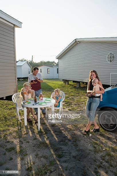 Families enjoying a cookout in front of trailer home