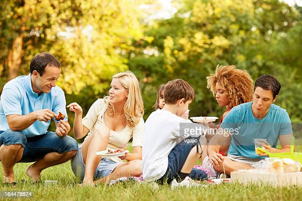 families enjoying eating at picnic. - dog eats out girl stock pictures, royalty-free photos & images