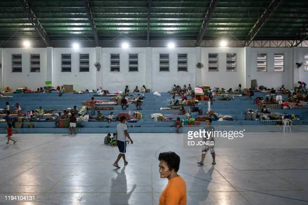 Families evacuated from the vicinity of the Taal volcano rest in the La Consolacion College gymnasium evacuation centre in Tanauan on Janaury 17 2020...