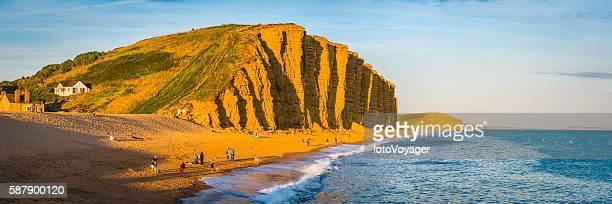 Families fishermen on beach beneath golden cliffs West Bay Dorset