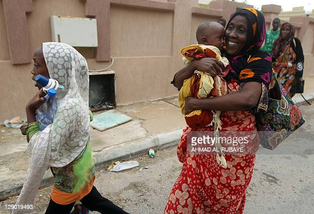 Families flee the area during heavy fighting between Libya's new regime fighters and forces loyal to Moamer Kadhafi in the city of Sirte on October...