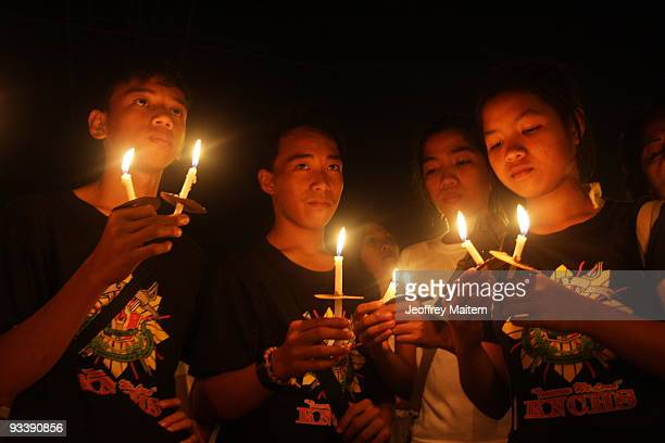 Families friends students and sympathizers light candles for those who died during a politically motivated massacre in nearby Ampatuan town yesterday...