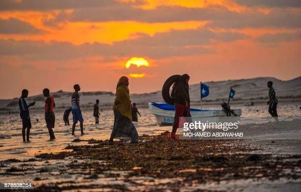 Families gather during sunset at Jazera Beach which has now become a popular spot on the outskirts of Mogadishu on November 2017 / AFP PHOTO /...