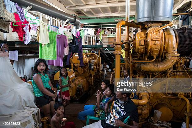 Families gather in their makeshift sleeping area in the hull of a tanker that ran aground in a particularly badly damaged part of Tacloban on...