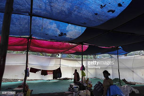 Families gather inside a temporary suburban camp, set up by local political party Shiv Sena for the rural poor traveling to Mumbai to find water, in...