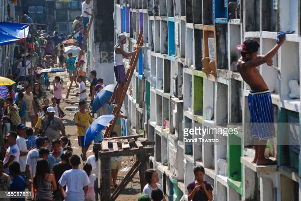 Families gather to pray light candles and clean tombstones of the departed at the Navotas public cemetery on November 1 2011 in Manila Philippines...