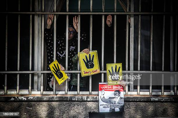 Families gesture the yellow Rabaa sign from their home to anti-coup marches in Cairo.