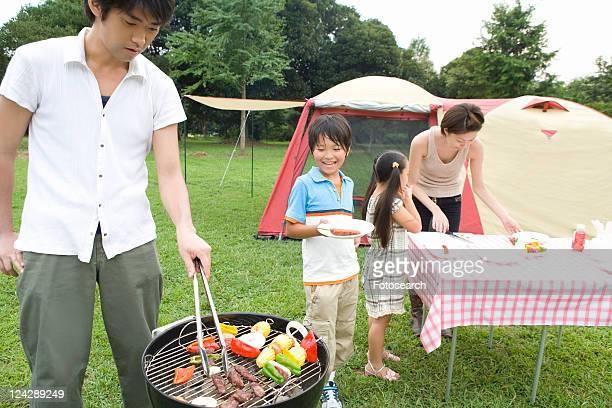 Families Having BBQ on Grass Field