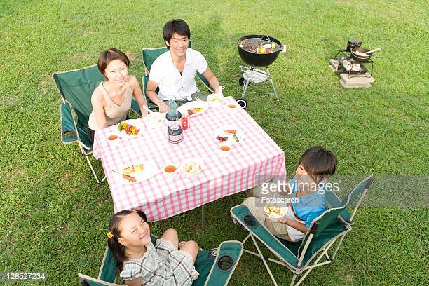 Families Having Lunch at Table on Grass Field
