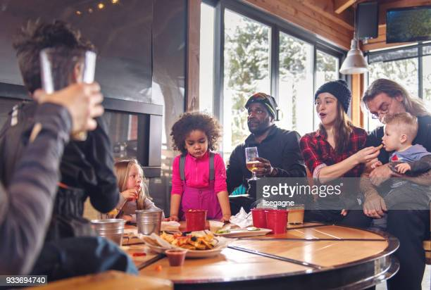 families in a ski resort, apres-ski relaxing - apres ski stock pictures, royalty-free photos & images