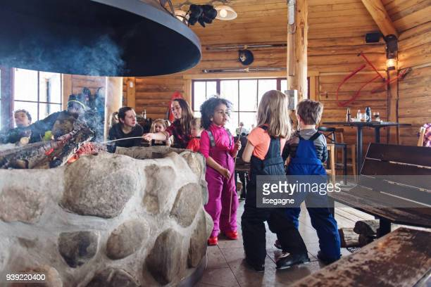 families in a ski resort, apres-ski relaxing - ski resort stock pictures, royalty-free photos & images