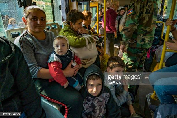 Families inside the buses prepared for their evacuation to Yerevan after increasing the azeri shelling over the city of Stepanakert during the...