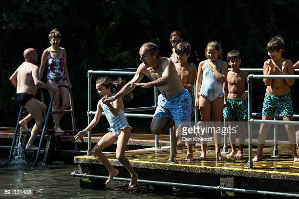 Families jump in the water at Parliament Hill mixed bathing ponds on August 17 2016 in London England Brits have been enjoying several days of warm...