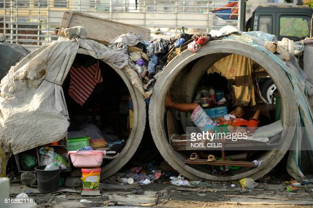 TOPSHOT Families live in concrete pipes used as makeshift dwellings along a street in Manila on March 22 2016 Roughly one quarter of the nation's 100...