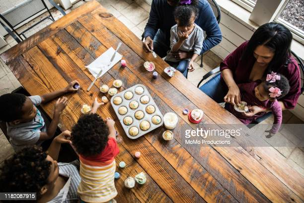 Families making cupcakes at birthday party