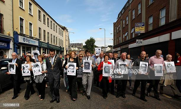 Families of the victims of the Bloody Sunday shootings march from the Bogside area of Londonderry to the Guildhall holding photographs of their...