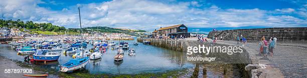 Families on holiday at seaside harbour Lyme Regis Cobb Devon