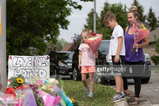Families pay their respects on June 8 at a makeshift memorial near the site where a man driving a pickup truck struck and killed four members of a...