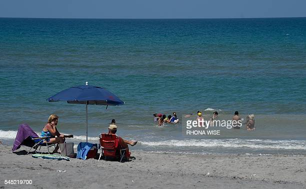 Families play in the ocean at Hobe Sound Beach a day after a ban on swimming was lifted due to a bluegreen algae bloom plaguing the water in Hobe...
