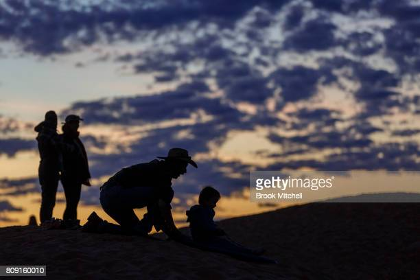 Families play on the vast sand dunes behind the Big Red Bash music festival site on July 5 2017 in Birdsville Australia