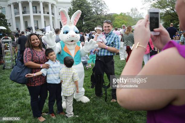 Families pose for photographs with one of the costumed Easter Bunny characters during the 139th Easter Egg Roll on the South Lawn of the White House...