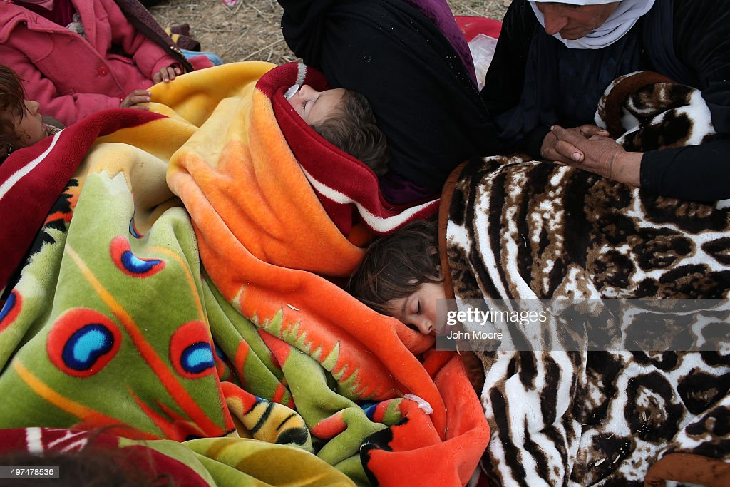 Families rest while fleeing from their ISIL or Daesh-held frontline village to a Kurdish-controled area on November 16, 2015 to Sinjar, Iraq. Peshmerga forces carefully screened the displaced Iraqis as they arrived, fearing enemy infiltrators and suicide bombers. Kurdish forces, with the aid of massive U.S.-led coalition airstrikes, liberated Sinjar from ISIL extremists, known in Arabic as Daesh, moving the frontline south. About a thousand villagers in Ghabosyeh fled north to Kurdish held territory, to take refuge camps or onward as refugees to Turkey or Europe.