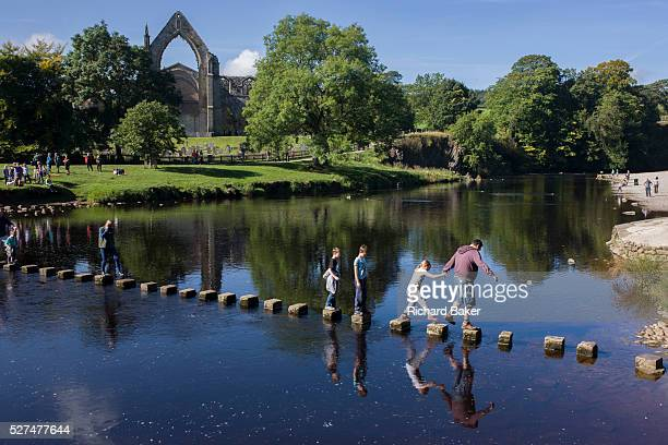 Families risk falling in the River Wharfedale while walking over the stepping stones at Augustinian Bolton Priory North Yorkshire Carefully stepping...