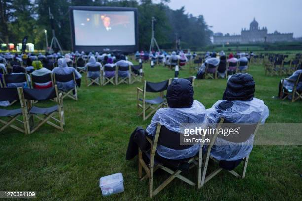 Families sit in heavy rain as they attend a screening of The Greatest Showman during the Luna Cinema movie experience at Castle Howard on September...