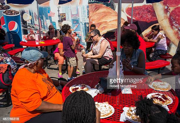 Families sit while eating food along the boardwalk July 24 2015 at Coney Island Beach in the Brooklyn borough of New York