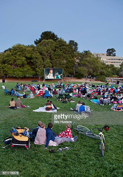 Families sitting in a park watching an outdoor movie