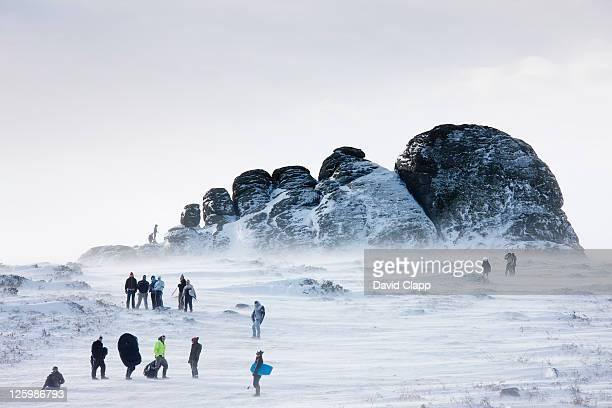 families skiing and tabogganing down the east face of haytor rocks after rare heavy snowfall, dartmoor, devon, england, uk, february 2009 - february stock pictures, royalty-free photos & images
