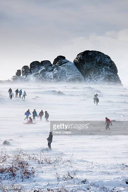 Families skiing and tabogganing down the east face of Haytor Rocks after rare heavy snowfall, Dartmoor, Devon, England, UK, February 2009