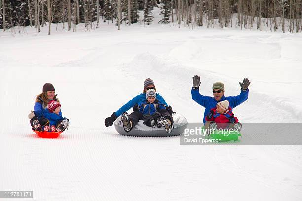 Families snow sledding and tubing