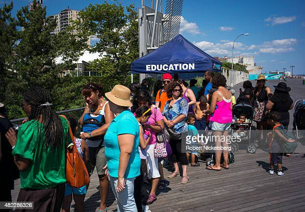 Families stand in line for an conservation venue along the boardwalk July 24 2015 at Coney Island Beach in the Brooklyn borough of New York