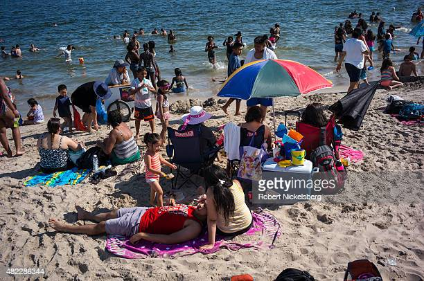 Families swim in the Atlantic Ocean and lie on the sand July 24 2015 at Coney Island Beach in the Brooklyn borough of New York