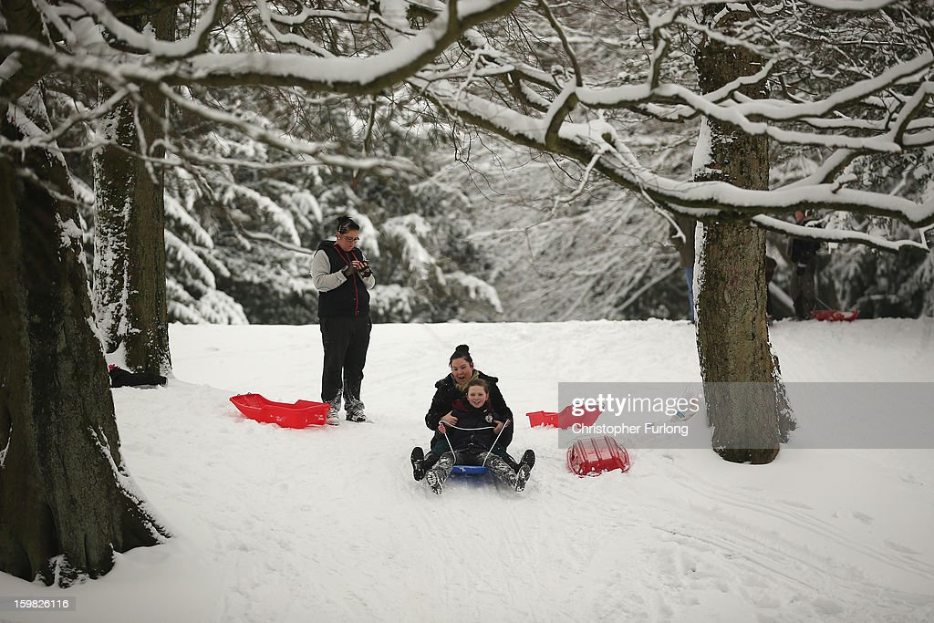 Families take advantage of the snow and go sledging in The Pavilion Gardens on January 21, 2013 in Buxton, United Kingdom. The Met Office has issued a red weather warning for parts of the Uk and advising against all non-essential travel as up to 30cm of snow is expected to fall in some areas today. The adverse weather has closed nearly 5,000 schools and caused many airports to cancel flights.