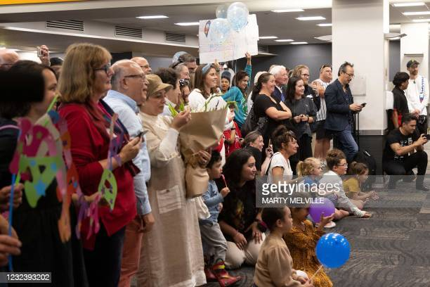 Families wait to be reunited as travellers arrive on the first flight from Sydney, in Wellington on April 19 as Australia and New Zealand opened a...